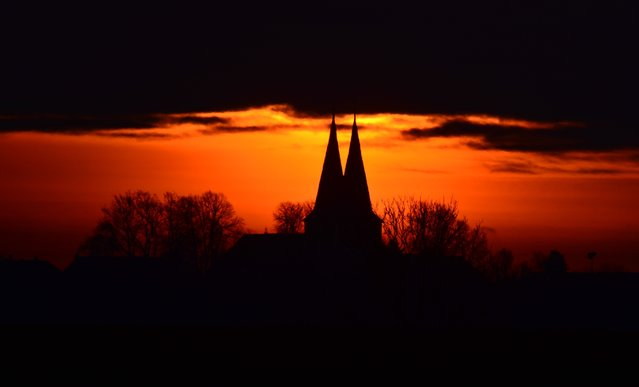 The St. Lawrence Church against a brightly colored morning sky in Hohenhameln, Germany, January 28, 2015. (Photo by Julian Stratenschulte/EPA)