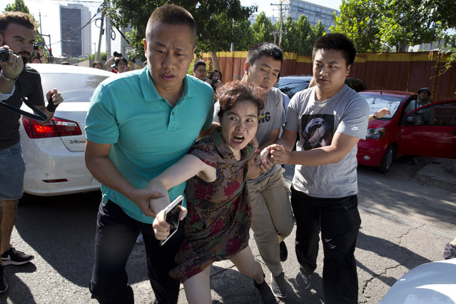 A woman is dragged away by Chinese men moments after she was seen talking to journalists near the site of a reported explosion outside the U.S. Embassy in Beijing, China, Thursday, July 26, 2018. A man exploded a small homemade bomb outside the U.S. Embassy in Beijing on Thursday, injuring only himself, according to police and an embassy spokesperson. (Photo by Ng Han Guan/AP Photo)