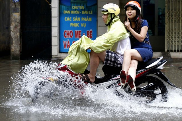 A couple ride a motorcycle along a flooded road after heavy rains caused by tropical storm Mangkhut in Hanoi, Vietnam, on August 9, 2013. (Photo by Reuters)
