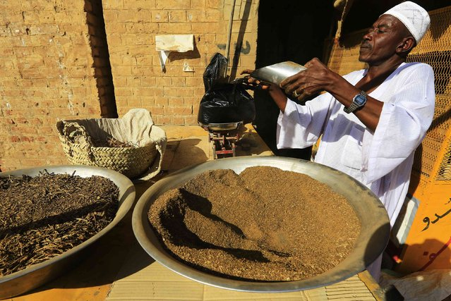 A trader weighs tobacco at a market in el-Fasher, in North Darfur February 5, 2015. (Photo by Mohamed Nureldin Abdallah/Reuters)