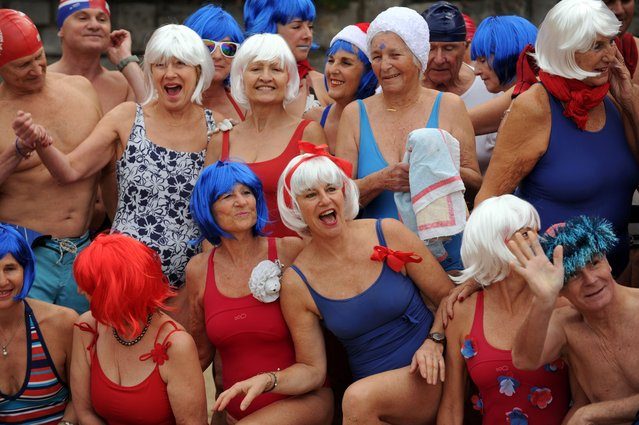 """People pose with colourful wigs at the beach of Port Vieux in Biarritz, southwestern France, on December 27, 2015 during a traditional Christmas Swim organised since 1929 by """"Les Ours blancs"""" (polar bears) association. (Photo by Iroz Gaizka/AFP Photo)"""