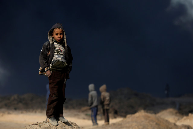 A boy stands in front of oilfields burned by Islamic State fighters in Qayyara, south of Mosul, Iraq November 23, 2016. (Photo by Goran Tomasevic/Reuters)