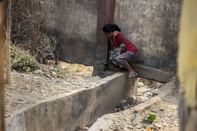 An unidentified woman used a drain hole to cross into Myanmar from the Champhai village in Mizoram, India, Saturday, March 20, 2021. (Photo by Anupam Nath/AP Photo)