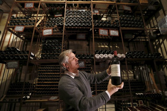 Remi Edange, manager at Domaine de Chevalier, presents a bottle of red wine in the cellar of Chateau Domaine de Chevalier (Graves Pessac Leognan label) in Leognan, near Bordeaux, southwestern France, February 10, 2015. The French Federation of Wine and Spirits Exporters (FEVS) will present the 2014 French wine and spirits annual exports during a news conference on Wednesday. (Photo by Regis Duvignau/Reuters)