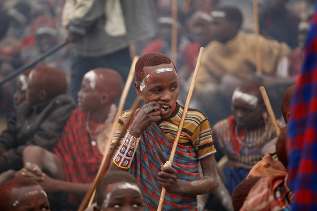 A Maasai boy eats meat during an initiation into an age group ceremony near the town of Bisil, Kajiado county, Kenya on August 23, 2018. (Photo by Baz Ratner/Reuters)