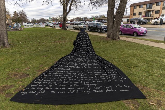 San Francisco-based artist Liney D draws attention to social injustice by wearing a cape with her story written on it, in front of the Brooklyn Central Police Station in Brooklyn Center, Minnesota on April 15, 2021. Kim Potter, the policewoman who shot dead Daunte Wright in a Minneapolis suburb after appearing to mistake her gun for her Taser, was arrested on Wednesday on manslaughter charges. Minneapolis has been roiled by nightly violent protests after Potter's shooting of Wright in his car on Sunday. (Photo by Kerem Yucel/AFP Photo)