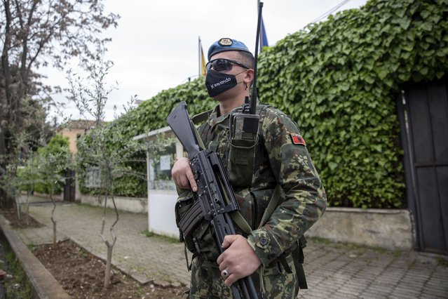 A member of the Albanian army secures the Spanish embassy ahead of the general elections in Tirana, Saturday, April 24, 2021. Albania holds parliamentary elections on Sunday amid the virus pandemic and a bitter political rivalry between the country's two largest political parties but that will serve as a key milestone in the country's next step toward European Union membership. (Photo by Visar Kryeziu/AP Photo)
