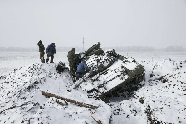 Members of the separatist self-proclaimed Donetsk People's Republic army collect parts of a destroyed Ukrainian army tank in the town of Vuhlehirsk, about 10 km (6 miles) to the west of Debaltseve, February 16, 2015. (Photo by Baz Ratner/Reuters)