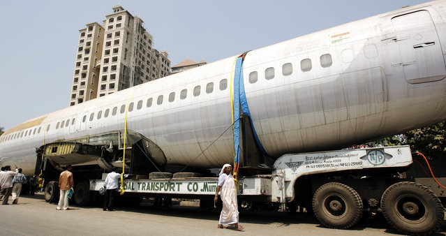 People walk past the fuselage of a Boeing 737 parked on a road in Mumbai May 3, 2007. The trailer carrying the fuselage got stuck on a narrow road in Mumbai three days ago while being taken to New Delhi. (Photo by Arko Datta/Reuters)