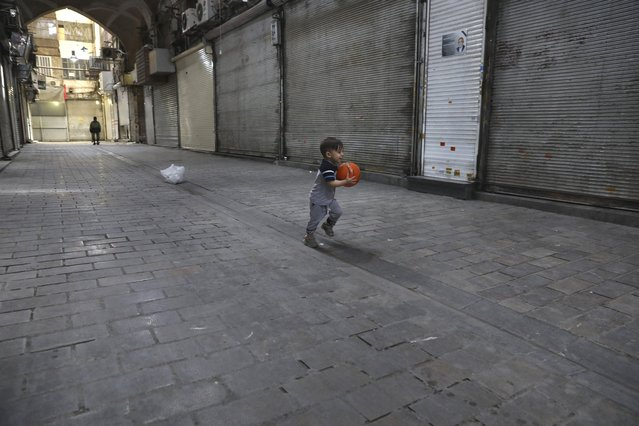 Arman, 2, plays in front of closed shops of Tehran's Grand Bazaar, Iran, Saturday, April 10, 2021. Iran on Saturday imposed partial lockdown on businesses in major shopping centers as well as intercity travels through personal cars in major cities including capital Tehran as it struggles with the worst outbreak of the coronavirus in the Mideast region. (Photo by Vahid Salemi/AP Photo)