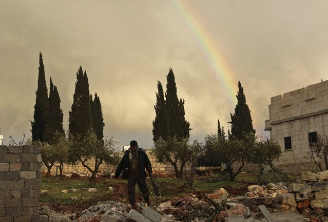 A rebel fighter carries his weapon as he walks in front of a rainbow in Ratian village, north of Aleppo, after what the rebels said was an offensive against them by forces loyal to Syria's President Bashar al-Assad that attempted to advance in the village but failed to February 18, 2015. (Photo by Ammar Abdullah/Reuters)