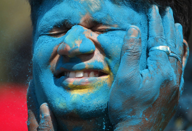 An Indian man closes his eyes as colored powder is smeared on his face during Holi festivities in Ahmadabad, India, Friday, March 6, 2015. Holi, India's joyful and colorful celebration of the arrival of spring along with several religious myths and legends, has long ago ceased to be only a Hindu festival. The streets and lanes across most of India turn into a large playground where people off all faiths throw colored powder and water at each other. (AP Photo/Ajit Solanki)