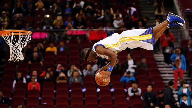 A member of the Flying Dubs, an acrobatic dunk team of the Golden State Warriors, performs before their NBA Global Game against the Los Angeles Lakers in Beijing, on Oktober 15, 2013. (Photo by Kim Kyung-Hoon/Reuters)