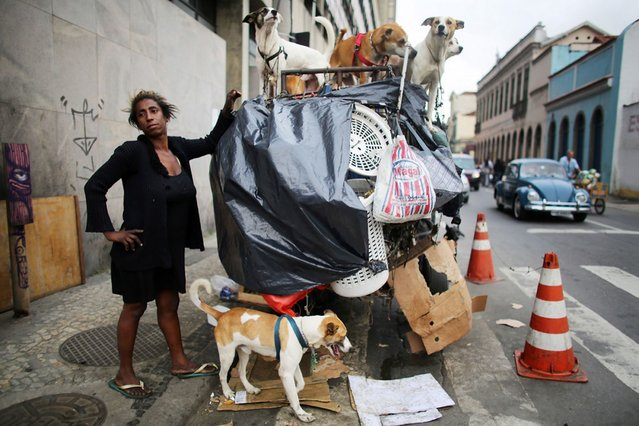 Rosana Moses stands with the family of 16 dogs she cares for in Rio de Janeiro, Brazil. She lives on the streets and relies on donations to help care for the dogs, on Oktober 30, 2013. (Photo by Mario Tama/Getty Images)