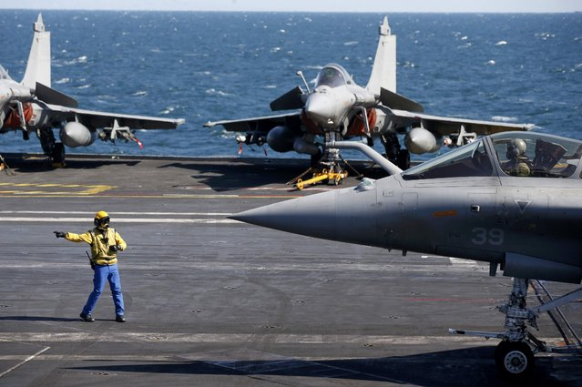 """A """"yellow dog"""" flight deck officer directs a Rafale fighter jet that prepares to take off aboard France's Charles de Gaulle aircraft carrier which continues its mission in the Gulf, January 28, 2016. (Photo by Philippe Wojazer/Reuters)"""