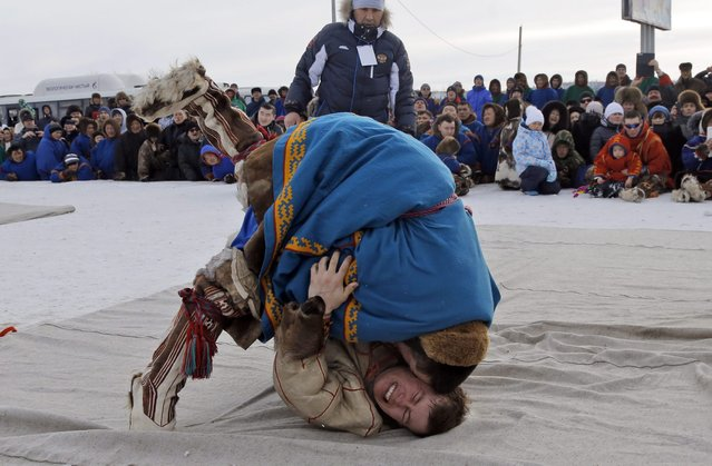 In this photo taken on Saturday, March 14, 2015, Nenets men wrestle during a competition at the Reindeer Herder's Day in the city of Nadym, in Yamal-Nenets Region, 2500 kilometers (about 1553 miles) northeast of Moscow, Russia. (Photo by Dmitry Lovetsky/AP Photo)