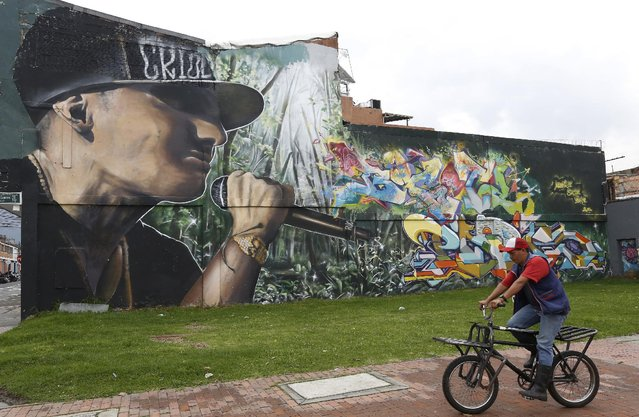 In this March 18, 2015 photo, a man rides past a wall painted by street artists, in Bogota, Colombia. (Photo by Fernando Vergara/AP Photo)
