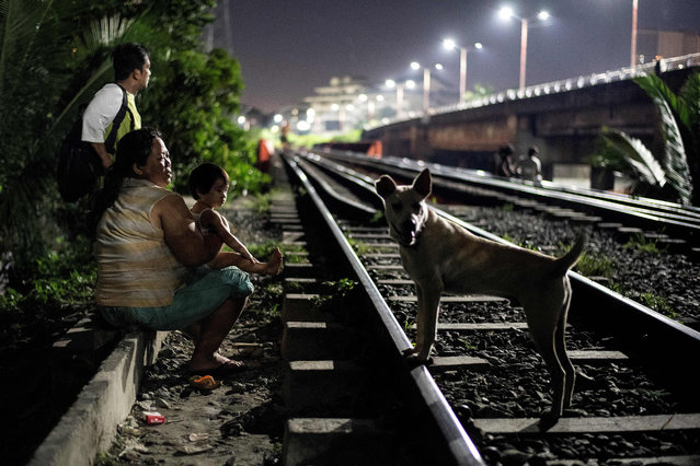 This picture taken on October 18, 2018 shows a mother (L) and child sitting along a train track in Manila, Philippines. (Photo by Noel Celis/AFP Photo)