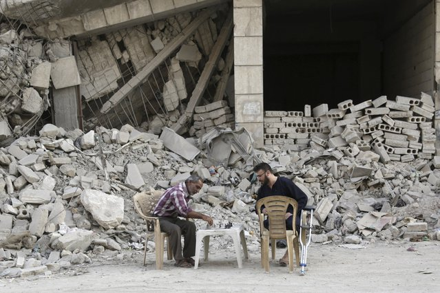 Men play chess in front of a damaged building in the rebel-controlled area of Maaret al-Naaman town in Idlib province, Syria October 19, 2015. (Photo by Khalil Ashawi/Reuters)