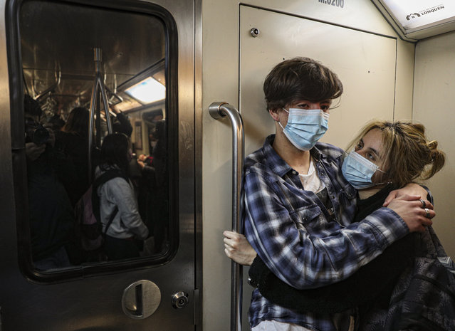 A couple wearing masks to curb the spread of the new coronavirus, embraces as they travel the subway, late afternoon in Santiago, Chile, on Wednesday, July 14, 2021. (Photo by Esteban Felix/AP Photo)