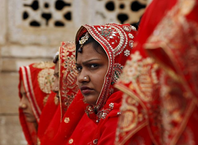 A Muslim bride looks on as she waits for the start of a mass marriage ceremony in the western Indian city of Ahmedabad March 21, 2015. (Photo by Amit Dave/Reuters)