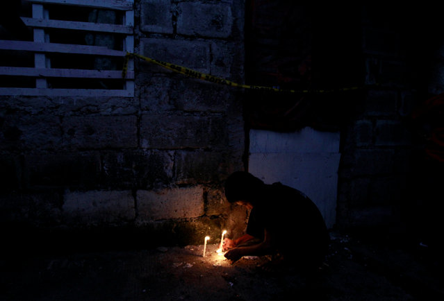 A resident lights a candle at the site where seven people were shot dead by suspected vigilantes at a house storing illegal narcotics, police said on Thursday, in Caloocan city, Metro Manila, December 31, 2016. (Photo by Czar Dancel/Reuters)