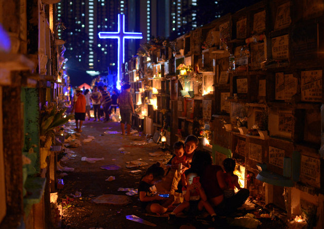 Filipino families visit the graves of their departed loved ones during All Saints Day in a public cemetery in Makati City, Metro Manila, Philippines, November 1, 2018. (Photo by Eloisa Lopez/Reuters)