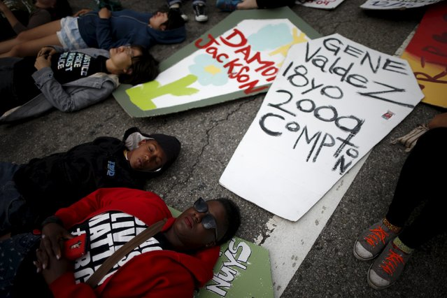 """People stage a """"die-in"""" in the middle of the road after carrying cutouts of coffins during a march to commemorate the more than 617 people they say have been killed by law enforcement in LA County since 2000, in Los Angeles, California April 7, 2015. (Photo by Lucy Nicholson/Reuters)"""