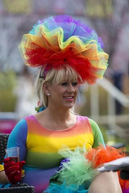 A spectator wears a multi coloured outfit during Aintree race meeting's Ladies Day the day before the Grand National horse race at Aintree Racecourse Liverpool, England, Friday, April 10, 2015. (Photo by Jon Super/AP Photo)