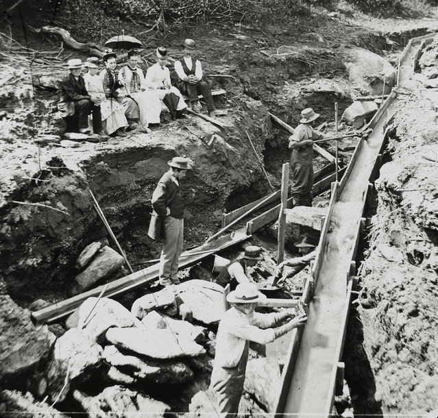 In this 1887 photo provided by the Plymouth Historical Society, a small audience watches men setting up a long box for gold prospecting in a stream in the Five Corners area of Plymouth, Vt. A growing number of people, especially in New England and the Pacific Northwest, are returning to streams in search of gold. (Photo by E.G. Davis collection/Plymouth Historical Society via AP Photo)