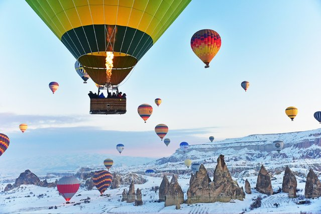 Hot-air balloons glide above fairy chimneys in snow-covered Cappadocia region, located in Central Anatolia's Nevsehir province, Turkey on January 19, 2019. (Photo by Murat Oner Tas/Anadolu Agency/Getty Images)