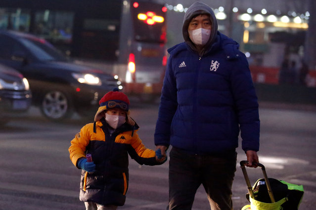 People wear face masks as they cross a street on a polluted day in Beijing, China January 4, 2017. (Photo by Thomas Peter/Reuters)