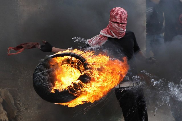 "A Palestinian sets fire to a tyre during clashes between hundreds of Palestinians and Israeli soldiers outside the Ofer prison after a march marking the 65th Nakba day or ""Day of Catastrophe"" on May 15, 2013 in Betunia near the West Bank city of Ramallah. (Photo by Abbas Momani/AFP Photo)"