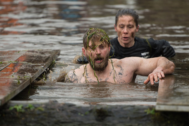 A competitor negotiates a water obstacle in the Tough Guy endurance event near Wolverhampton, central England, on January 27, 2019. (Photo by Oli Scarff/AFP Photo)