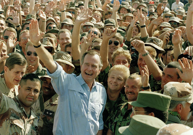In this November 22, 1990 file photo, President George Bush poses with soldiers during a stop at an air base in Dhahran, Saudi Arabia. Twenty five years after the first U.S. Marines swept across the border into Kuwait in the 1991 Gulf War, American forces find themselves battling the extremist Islamic State group, born out of al-Qaida, in the splintered territories of Iraq and Syria. Saddam Hussein, demonized as being worse than Adolf Hitler by President George H.W. Bush, would outlast his American rival in power until Bush's son launched the 2003 American-led invasion that toppled the Iraqi dictator. (Photo by J. Scott Applewhite/AP Photo)