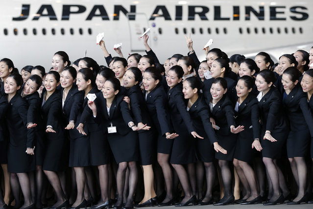 Japan Airlines Co. (JAL) group companies' new employees pose for photographs in front of a JAL aircraft during a welcoming ceremony at the company's hangar near Haneda Airport in Tokyo, Japan, on Monday, April 1, 2013. (Photo by Kiyoshi Ota/Bloomberg)