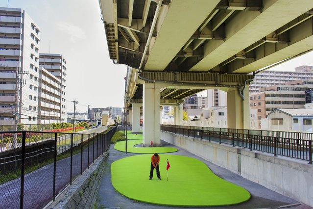 A man plays minigolf underneath an overpass on a sunny spring day in Tokyo April 16, 2015. (Photo by Thomas Peter/Reuters)