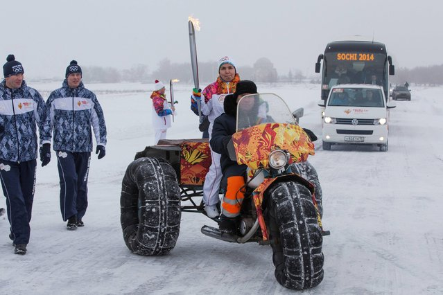 In this photo provided by Olympictorch2014.com, torch bearer Alfiya Aliyeva carries an Olympic torch on a vehicle as she reaches Bolgar on the Volga River, Russia, Monday, December 30, 2013. The 65,000-kilometer (40,389 mile) Sochi torch relay, which started on October 7, is the longest in Olympic history. The torch has traveled to the North Pole on a Russian nuclear-powered icebreaker and has even been flown into space. (Photo by AP Photo/Olympictorch2014.com)