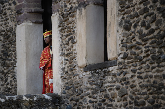 A trainee Ethiopian Orthodox priest looks out from the tower at Fasilides Bath as he awaits the arrival of the Tabot procession during the annual Timkat epiphany celebration on January 18, 2017 in Gondar, Ethiopia. (Photo by Carl Court/Getty Images)