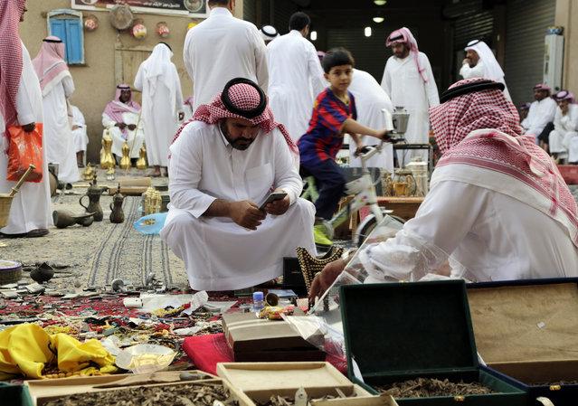 In this April 16, 2015 photo, 2015, a Saudi buyer talks to a vendor at al-Aqeeliya open-air auction market, in Riyadh, Saudi Arabia. (Photo by Hasan Jamali/AP Photo)