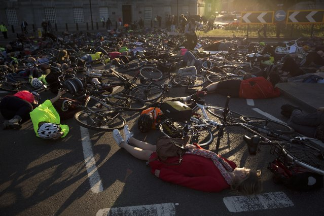 "Cyclists lie in the street as they take part in a ""die-in"" vigil in memory of cyclist Moira Gemmill who died after being hit by a tipper truck on April 9, on a roundabout on the junction of Millbank and Lambeth Bridge in central London, Monday, April 20, 2015. Gemmill, aged 55 and the former head of design at the Victoria and Albert Museum, was the fifth cyclist killed in a collision with a vehicle in London this year. (Photo by Matt Dunham/AP Photo)"