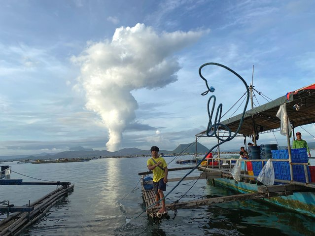 A Filipino villager boy throws a line next to the rumbling Taal Volcano as it emits smoke at a fishing village in the town of Laurel, Batangas province, Philippines, 05 July 2021. According to the Philippine Institute of Volcanology and Seismology (Phivolcs) latest bulletin on July 04 the highest level of volcanic sulfur dioxide gas emission was recorded at the Taal volcano and eruption may occur anytime soon. More than 3,000 residents from high-risk villages were evacuated after the volcano started spewing steam, filling the air with toxic gas and prompting health warnings. (Photo by Francis R. Malasig/EPA/EFE)