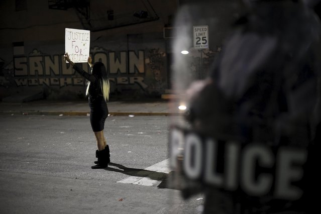 """A woman holds a """"Justice for Freddie"""" sign next to graffiti that reads, """"Sandtown Winchester"""" near Baltimore Police Department Western District during a protest against the death in police custody of Freddie Gray in Baltimore April 25, 2015. (Photo by Sait Serkan Gurbuz/Reuters)"""