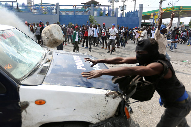 A demonstrator throws a rock at a police car during a protest against former government officials accused of misusing Petrocaribe funds and the country's inflation rate in Port-au-Prince, Haiti February 7, 2019. (Photo by Jeanty Junior Augustin/Reuters)