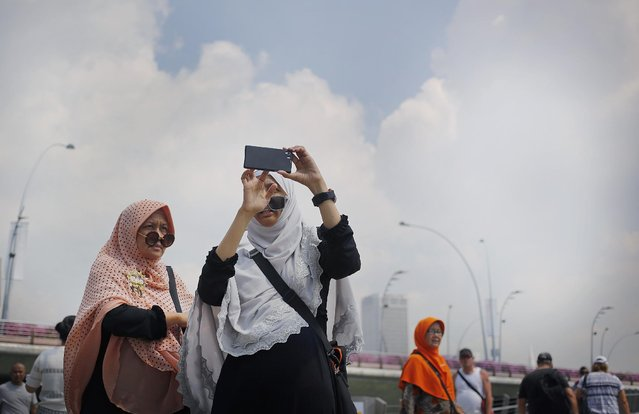 Tourists check photos taken of themselves on their smart phones at a popular tourist spot, Tuesday, April 21, 2015, in Singapore. (Photo by Wong Maye-E/AP Photo)