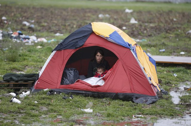 Migrants rest in a tent at a makeshift camp on the Greek-Macedonian border, near the village of Idomeni, Greece March 10, 2016. (Photo by Stoyan Nenov/Reuters)