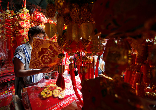 Ethnic Chinese-Thai people looks at decorations as preparations are underway for celebrations of the upcoming Lunar New Year or Spring Festival in Chinatown, Bangkok, Thailand, 02 February 2019. The Chinese Lunar New Year falls on 05 February this year and will mark the beginning of the Year of the Pig. (Photo by Narong Sangnak/EPA/EFE)