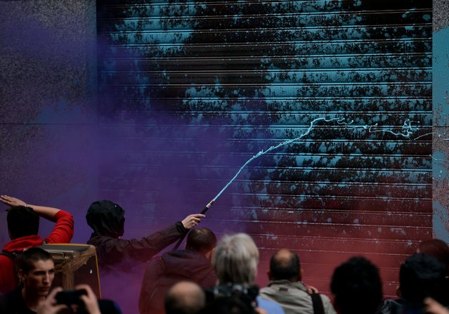 A masked demonstrator sprays color on a shop door during a demonstration in downtown Milan on April 30, 2015 to protest against the World Exposition Milano 2015 (Universal Exposition) saying that the massively indebted Italian state should not be ploughing money into an ephemeral event at a time of economic hardship for many Italians. (Photo by Filippo Monteforte/AFP Photo)