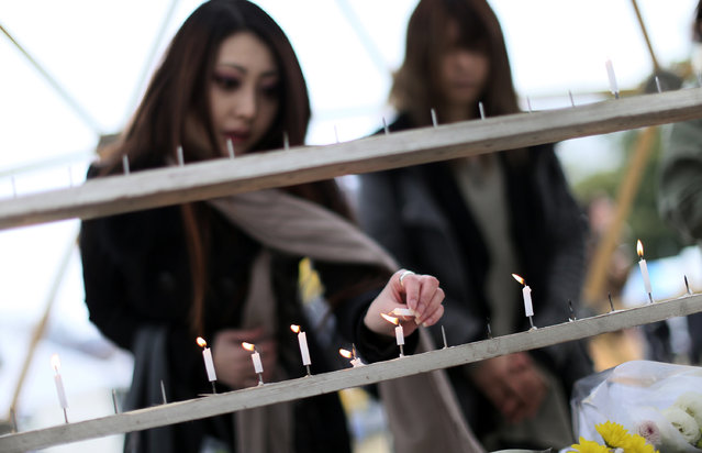 A woman lights a candle to mourn for the victims of the March 11, 2011 earthquake and tsunami prior to a special memorial event Friday, March 11, 2016.  Japan on Friday marked the fifth anniversary of the 2011 tsunami that killed more than 18,000 people and left a devastated coastline along the country's northeast that has still not been fully rebuilt. (Photo by Eugene Hoshiko/AP Photo)