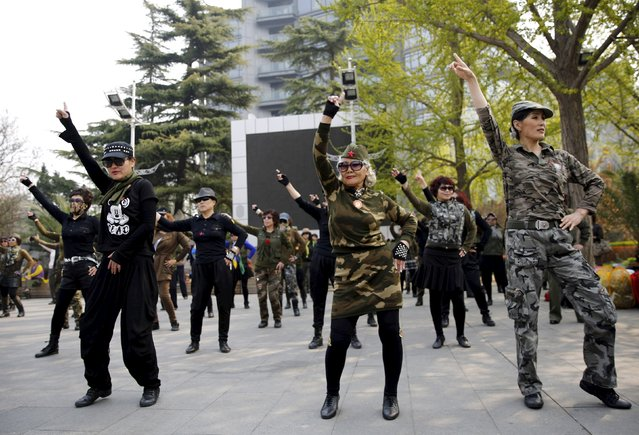 Seventy-nine-year-old Wang Baorong (C), dressed in military style clothes, and other participants perform square dancing at a park square in Beijing, China, April 9, 2015. (Photo by Kim Kyung-Hoon/Reuters)